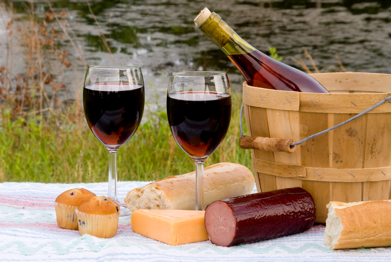 Glasses of red wine, cheese, baguette and French sausage